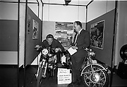 26/06/1967<br /> 06/26/1967<br /> 26 June 1967<br /> Motoring Enthusiasts Week officially opened by Joe Lynch at the International Trade Promotion Centre, Dublin. Image shows Joe Lynch taking the racing position on a Bultaco 250cc Model TSS of the type that won 1st,2nd and 6th places in the 250cc Production T.T. race ridden by Mr Lindsay of Lindsay and Sons Ltd.. Also in the picture is Mr. C. Sommerville of Lindsay (Motor Cycles) Ltd..