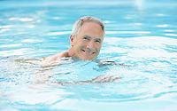 Middle-aged man swimming in pool portrait