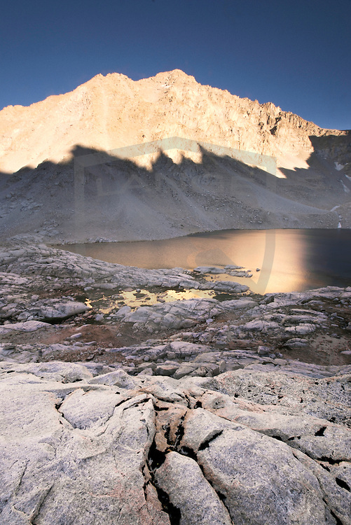 sunset light strikes a mountain peak above a lake in the sierra nevada mountains of mount whitney in california.