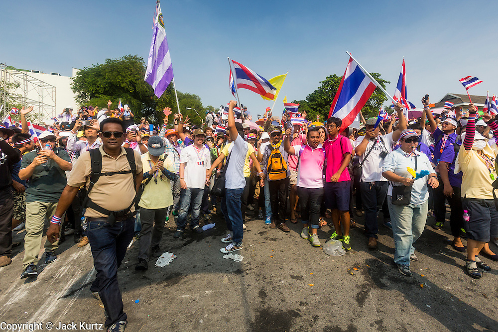 "09 DECEMBER 2013 - BANGKOK, THAILAND: Anti-government protestors march to the gates of Government House in Bangkok. Thai Prime Minister Yingluck Shinawatra announced she would dissolve the lower house of the Parliament and call new elections in the face of ongoing anti-government protests in Bangkok. Hundreds of thousands of people flocked to Government House, the office of the Prime Minister, Monday to celebrate the collapse of the government after Yingluck made her announcement. Former Deputy Prime Minister Suthep Thaugsuban, the organizer of the protests, said the protests would continue until the ""Thaksin influence is uprooted from Thailand."" There were no reports of violence in the protests Monday.      PHOTO BY JACK KURTZ"