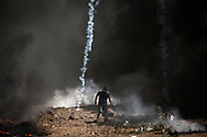 Tear gas canisters rain around a Palestinian walking away of the border fence with Israel as mass demonstrations continue on May 14, 2018 in Gaza City, Gaza. Israeli soldiers killed at least 41 Palestinians and wounded over a thousand as the demonstrations coincided with the controversial opening of the U.S. Embassy in Jerusalem. This marks the deadliest day of violence in Gaza since 2014. Gaza's Hamas rulers have vowed that the marches will continue until the decade-old Israeli blockade of the territory is lifted