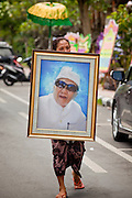 Apr. 25 -- UBUD, BALI, INDONESIA:  A member of the family carries a portrait of Cokorde Gede Raka at the funeral for Gede Raka, a member of Ubud's royal family Sunday, Apr. 25. Balinese are Hindus and cremate their dead. Balinese funerals are elaborate - and expensive - affairs. A funeral for one person costs a minimum of 45 million rupiah (about $5,000 US). The body is placed into the bull's body at the cremation and cremated in the bull. The funeral pyre is burnt adjacent to the bull. That is what a family may earn in two to three years. The result is that only the rich can afford formal cremations. The body (in the casket) is placed in the top of the funeral pyre and the procession takes the body to the cremation site. The funeral pyre, and the body, are spun at intersections to confuse the spirits so the soul doesn't try to return to its home and to confuse evil spirits.    PHOTO BY JACK KURTZ