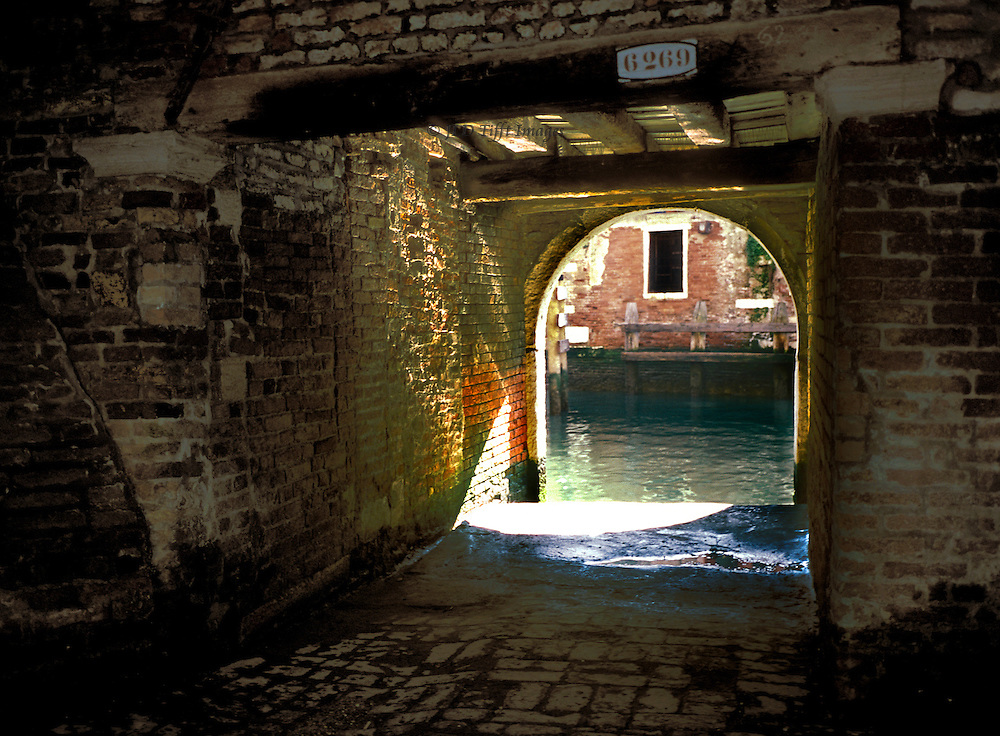 "Corte Boera, called ""Corte Sconta detta Arcana"" which Corto Maltese's author Mr Hugo Pratt gave to it.  View through the water gate to the canal.  Sunlight bouncing off the water dapples the brick walls of the entrance.."