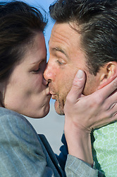 Close up of a woman surprising a man with a kiss