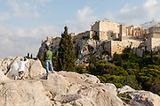 Young men photographing pigeon in the shadow of the acropolis, Athens, Greece.