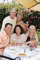 Five friends toasting at dining table outdoors