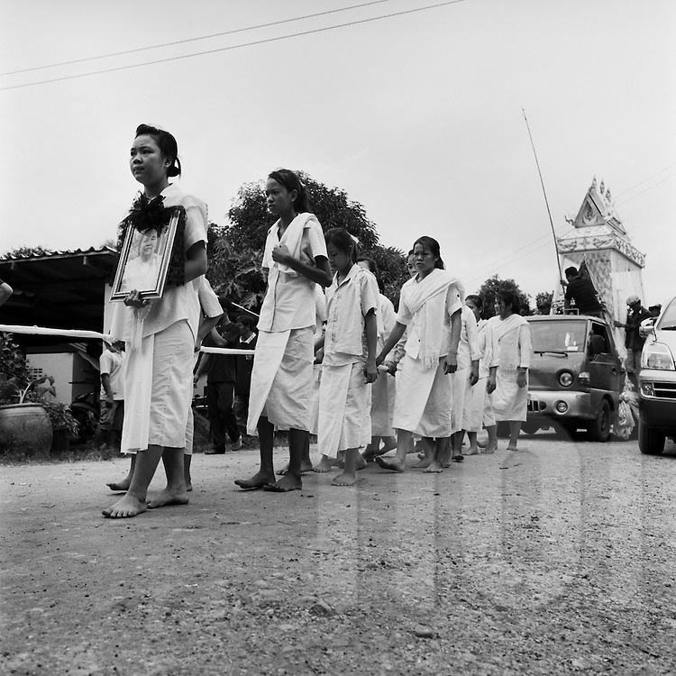 Funeral ceremony, Vientiane Province, Laos, Asia. Procession of sad women walking to the cemetery. The first one carries a portrait of the late. Coffin is in a truck behind.