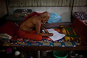 In a small monastery, an elder monk concentrates on his studies of the day.