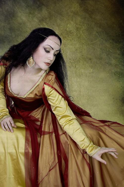 Beautiful Young Woman with long black hair wearing long dress reaching down with hand