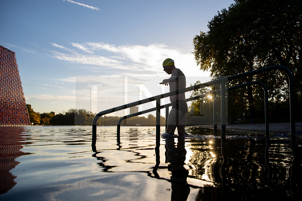 © Licensed to London News Pictures. 01/10/2018. London, UK. A swimmer enters the Serpentine Lido in Hyde Park at sunrise this morning. Temperatures in the capital were cold this morning, but are set to reach over 20 degrees Celsius later this week, higher than average for the time of year. Photo credit : Tom Nicholson/LNP