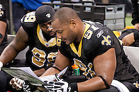 28 November 2011: (99) Aubrayo Franklin and (91) Will Smith of the New Orleans Saints look over defensive schemes on the sideline while playing against the New York Giants during the first half of the Saints 49-24 victory over the Giants at the Mercedes-Benz Superdome in New Orleans, LA.