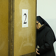 VENICE, ITALY - FEBRUARY 24:  A nun helps one of her old sisters to vote at a Polling Station in Venice Castello as the Italian General Election gets underway on February 24, 2013 in Venice, Italy. Italians are heading to the polls today to vote in the elections, as the country remains in the grip of economic problems . Pier Luigi Bersani's centre-left alliance is believed to be a few points ahead of the centre-right bloc led by ex-Prime Minister Silvio Berlusconi.  (Photo by Marco Secchi/Getty Images)
