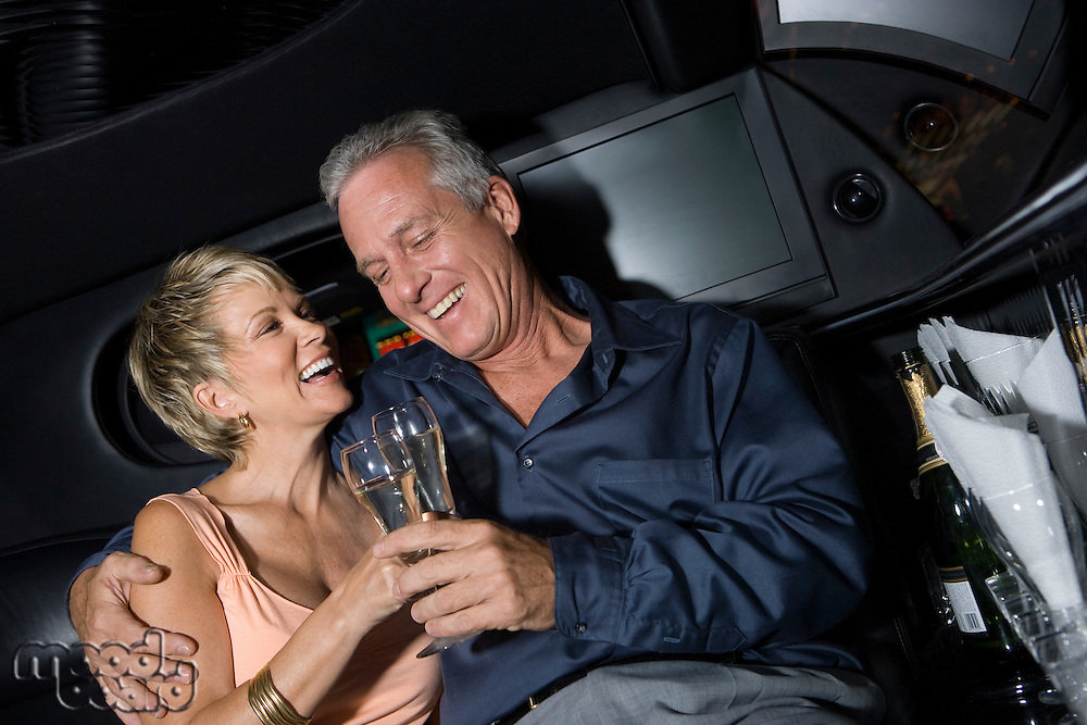 Middle-aged couple sitting on back seat of limousine and drinking champagne