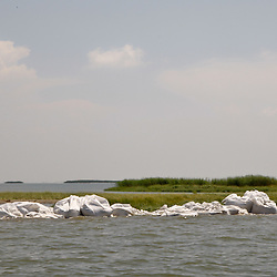 2,000 pound bags of sand are dropped along the shoreline to prevent oil from reaching further into marshlands by creating a barrier off the coast west of Venice, Louisiana, U.S., on Tuesday, June 15, 2010.  Oil from Deepwater Horizon spill continues to impact areas across the coast of gulf states. (Mandatory Credit: Derick E. Hingle).