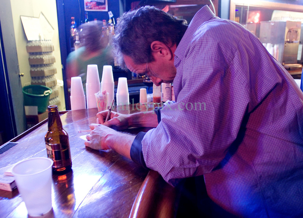 09 December, 05.  New Orleans, Louisiana. <br /> Columnist Chris Rose of the Times Picayune takes notes on a napkin in a music club late in the evening.<br /> Photo; ©Charlie Varley/varleypix.com