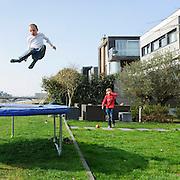 Nederland Amsterdam 29 maart 2011 20110329 Nieuwbouwwijk Ijburg, kinderen spelen, zij springen op een trampoline, in de achtertuin van een van de grote woningen met individuele architectuur die aan het water grenzen. Individueel vormgegeven architectuur. Noot: Fotograaf heeft toestemming gekregen van volwassene op de achtergrond om de beelden te maken.  , spelende, spelenderwijs, sportief, sportieve, sportive, springen, sprong, stadsdeel, stadsuitbreiding, stadswijk, sunny, sunshine, vastgoed, ventje, ventjes, vernieuwing, vinex, vinex-locaties, vinex-wijken, vinexbuurt, vinexlocatie, vinexlokatie, vinexwijk, voorgevel, voorjaar, vrij, vrije tijd, warm weer, wijk, wijken, wonen, woning, woningbehoefte, woningen, woningmarkt, woningvoorraad, woonbuurt, woonbuurten, woonlast, woonlasten, woonwijk, woonwijken, woz waarde, Youth, zichzelf vermaken, zonlicht, zonnetje, zonnig, zonnig weer, zonnige dag, zwevenFoto: David Rozing
