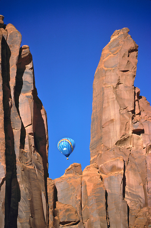 A blue hot-air balloon blends with the sky above Monument Valley, Utah.