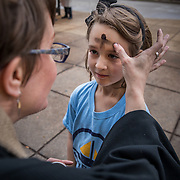 "ALEXANDRIA, VA - MAR1: Pastor Robin Anderson gives ""glitter ashes"" for Ash Wednesday to kindergarten student, Genevieve Dalton, 6, outside the Braddock Road metro station, in Alexandria, VA, March 1, 2017. Across the country, churches involved with the advocacy group Parity will be giving out ""glitter ashes"" to demonstrate that LGBT people should be included in Christianity.(Photo by Evelyn Hockstein/For The Washington Post)"