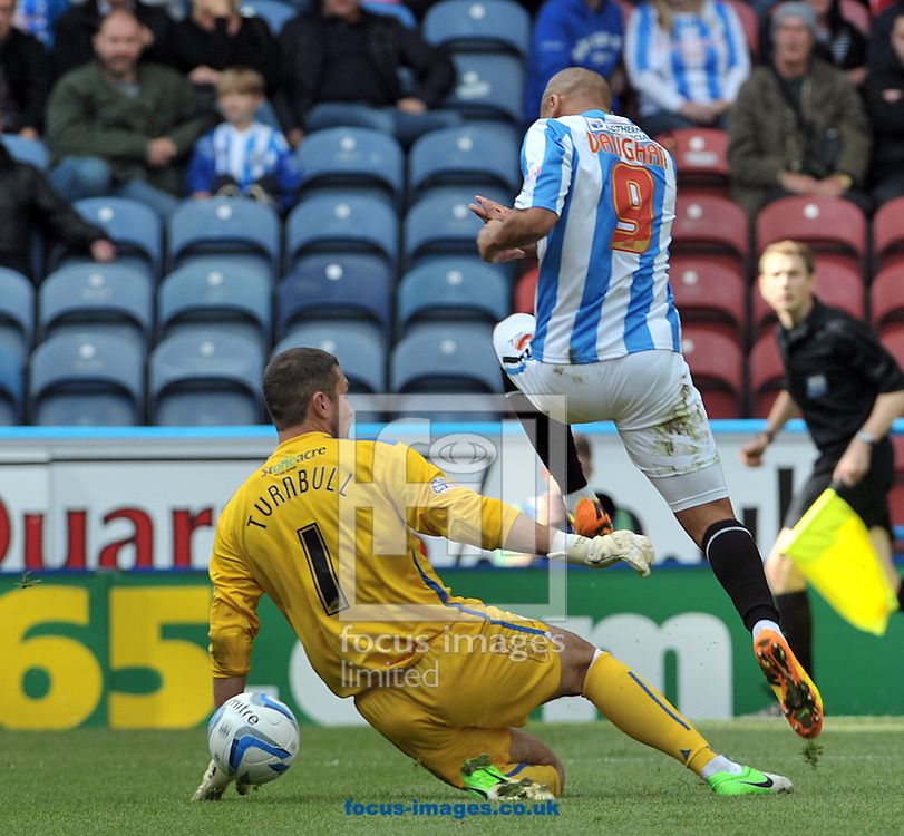 Picture by Graham Crowther/Focus Images Ltd +44 7763 140036<br /> 14/09/2013<br /> James Vaughn of Huddersfield Town rounds Ross Turnbull  of Doncaster Rovers during the Sky Bet Championship match at the John Smiths Stadium, Huddersfield.