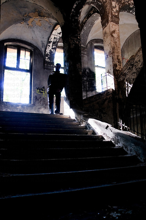 Silhouette of a man standing on some old stairs in a large building