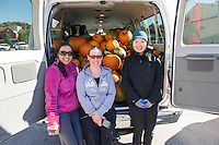 Lucy Le, Tammy Marquis and Hyun Choi from Plymouth Elementary School have their van loaded with 100 pumpkins to be carved for Laconia's Pumpkin Fest on Saturday.  (Karen Bobotas/for the Laconia Daily Sun)