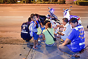 "02 OCTOBER 2009 -- BANGKOK, THAILAND: A boy waits for medics from Poh Teck Tung to help her mother after they were involved in a minor motorcycle accident in Bangkok. The 1,000 plus volunteers of the Poh Teck Tung Foundation are really Bangkok's first responders. Famous because they pick up the dead bodies after murders, traffic accidents, suicides and other unplanned, often violent deaths, they really do much more. Their medics respond to medical emergencies, from minor bumps and scrapes to major trauma. Their technicians respond to building collapses and traffic accidents with heavy equipment and the ""Jaws of Life"" and their divers respond to accidents in the rivers and khlongs of Bangkok. The organization was founded by Chinese immigrants in Bangkok in 1909. Their efforts include a hospital, college tuition for the poor and tsunami relief.   PHOTO BY JACK KURTZ"