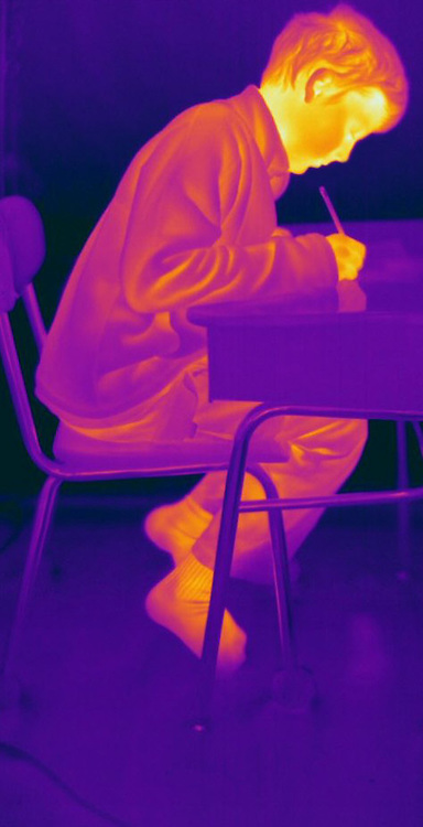 Thermogram of a boy student writing.  The different colors represent different temperatures on the object. The lightest colors are the hottest temperatures, while the darker colors represent a cooler temperature.  Thermography uses special cameras that can detect light in the far-infrared range of the electromagnetic spectrum (900?14,000 nanometers or 0.9?14 µm) and creates an  image of the objects temperature..