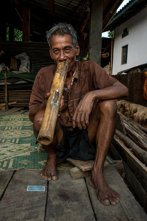 A man smokes a lage tobacco pipe in the village of Khoc Kham.