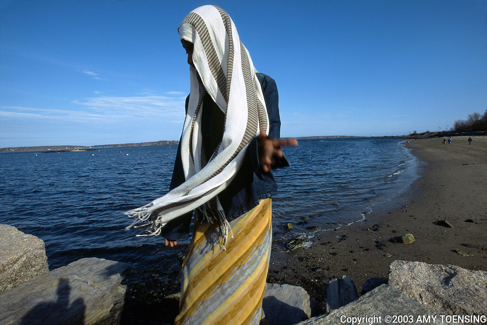 PORTLAND, ME - JUNE 01: High school sophomore Naima Abdulle catches her veil from flying away in the Maine ocean breeze on the East End Beach June 1, 2004 in Portland, Maine. Naima moved to Portland, Maine from Somalia with her family in 2001. As a Muslim female she is expected to uphold many of the customs and traditions of Islam in spite of the many influences from western culture. At the age of 17 she has chosen to get married and continue with her high school studies. (Photo by Amy Toensing) _________________________________<br /> <br /> For stock or print inquires, please email us at studio@moyer-toensing.com.