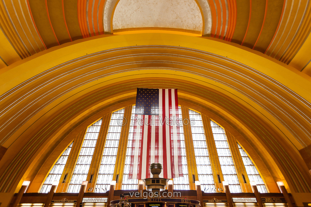 Interior photo of Cincinnati Museum Center at Union Terminal arched entrance and large American flag. Cincinnati Museum Center was originally a passenger railroad station and currently serves as a museum and theater. It is a Historic Landmark and is listed on the US National Register of Historic Places. Photo is high resolution and was taken in 2012.