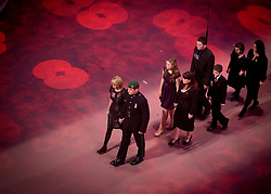 © Licensed to London News Pictures. 09/11/2013.  Bereaved family members are led into the Royal Albert Hall by the mother and brother of Lance Corporal James Ashworth who received a posthumous VC medal after being killed in Afghanistan.  Men and women from the UK Armed Forces take part in the 2013 Festival of Remembrance.  Bands from the Army, Navy and the Royal Air Force performed in front of Her Majesty The Queen.  Held in the Royal Albert Hall the service commemorated and honoured all those who have lost their lives in conflicts.    Photo credit: Alison Baskerville/LNP
