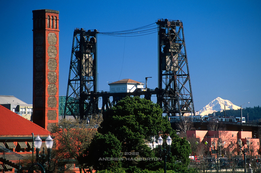 City of Portland skyline with MAX transit train crossing the Steel Bridge and distant Mount Hood, Oregon, USA.  The redbrick building in the foreground is Union Station.  Nikon F4; 70-300/4-5.6D. Fuji RVP.