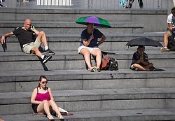 Image ©Licensed to i-Images Picture Agency. 04/07/2014. London, United Kingdom. Hot weather with 27ºC in the capital. People cover themselves from the strong sun with umbrellas while watching tennis in City Hall area. Central London. Picture by Daniel Leal-Olivas / i-Images
