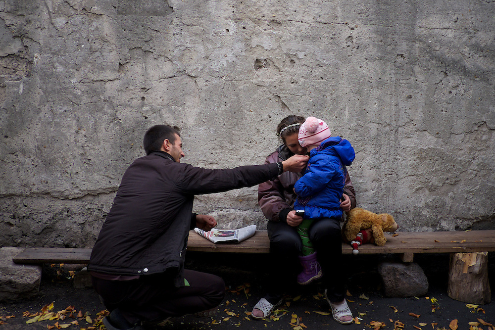 DONETSK, UKRAINE - OCTOBER 16, 2014: A family of IDPs at a bomb shelter in Petrovskiy district of Donetsk play outside the shelter during a pause in the fighting between DNR separatist combatants and the Ukrainian National Guard for the control of Donetsk city. More than one hundred people have been living for the past four months at the shelter. CREDIT: Paulo Nunes dos Santos