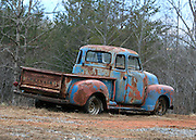 A 1950-something Chevrolet pick up truck sitting in a field near Blue Ridge Georgia.