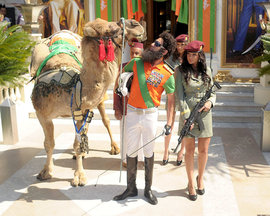 16.MAY.2012. CANNES<br /> <br /> SASCHA BARON COHEN WITH HIS SECURITY GIRLS LEAVES THE CARLTON HOTEL IN CANNES AND CLIMBS ONTO A CAMEL<br /> <br /> BYLINE: EDBIMAGEARCHIVE.COM<br /> <br /> *THIS IMAGE IS STRICTLY FOR UK NEWSPAPERS AND MAGAZINES ONLY*<br /> *FOR WORLD WIDE SALES AND WEB USE PLEASE CONTACT EDBIMAGEARCHIVE - 0208 954 5968*