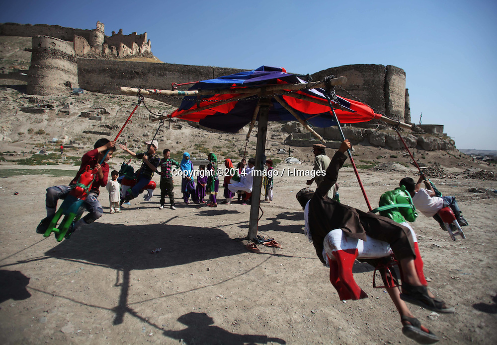 Image ©Licensed to i-Images Picture Agency. 28/07/2014. Kabul, Afghanistan. <br /> 61981790<br /> Afghan children enjoy playing on a merry-go-round during the Eid al-Fitr celebration in Kabul, Afghanistan, on July 28, 2014. Picture by  imago / i-Images<br /> UK ONLY