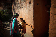 Radhika, left, 14, avoids touching others in her village as she takes a back path towards a water pump where girls practicing chaupadi are allowed to bath, in Siddheshwar village, Achham, Nepal.  During chaupadi, women may not use the regular village water sources, often walking long distances for obligatory daily washing.