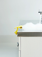 Yellow rubber gloves on edge of sink