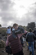 A young child from the Middle East is carried up a hill from the beach after the crowded boat she and others were traveling in arrived on the north coast of the Greek island of Lesbos from Turkey.