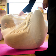 """TOKYO, JAPAN - JANUARY 29 : A woman wrapped during a workshop called """"Otonamaki"""", which directly translates to adult wrapping in Tokyo, Japan on Sunday, January 29, 2017. Otonamaki is a Japanese therapeutic method meant to alleviate posture problems and stiffness. (Photo by Richard Atrero de Guzman/ANADOLU Agency)"""