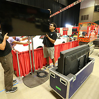 Pete White, left, and Lukas Thompson begin hanging the big screen monitors around the Toyota booth for this week's Caeer Fair at the BancorpSouth Arena Monday morning.