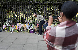© Licensed to London News Pictures. 05/08/2016. London, UK. People pose for photographs next to floral tributes at the spot in Russell Square where American Darlene Horton was killed and five others were injured. A Norwegian man of Somali heritage has been arrested.  Photo credit: Peter Macdiarmid/LNP