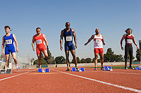 Athletes standing next to starting blocks, ready to run