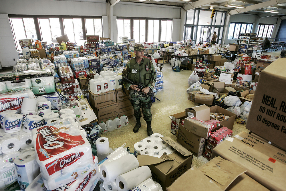 An armed National Guard secures a relief supplies depot set up at the Elementary School of Bay Saint Louis, Mississippi. 06 September 2005.