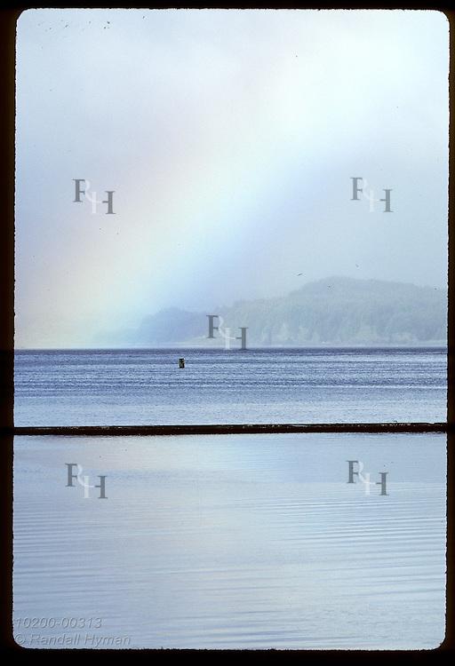 Rainbow soars skyward over Chiniak Bay as storm clears on a July morning; Kodiak Island. Alaska