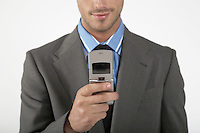 Businessman using mobile phone mid section
