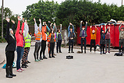 New Volunteers for Help Refugees UK go through their morning exercises and warm up before getting to work in the warehouse.  Help Refugees has grown out of #helpcalais, a social media campaign started by Lliana Bird (Radio X DJ), Dawn O'Porter (Writer and Presenter), Josie Naughton and Heydon Prowse (The Revolution will be Televised) to raise a few funds and collect goods to take to Calais to help in some small way. The public response to the campaign was huge, and we were quickly able to provide aid in Calais and far beyond.