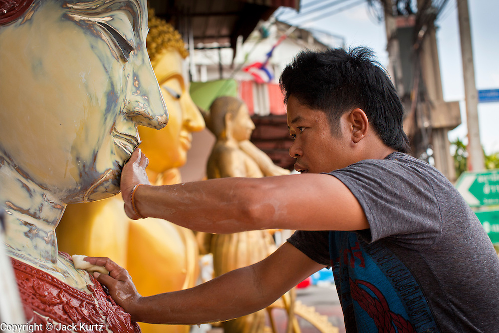 """05 JULY 2011 - BANGKOK, THAILAND:   A man paints a statue of a Buddha on Bamrung Muang Street in Bangkok. Thanon Bamrung Muang (Thanon is Thai for Road or Street) is Bangkok's """"Street of Many Buddhas."""" Like many ancient cities, Bangkok was once a city of artisan's neighborhoods and Bamrung Muang Road, near Bangkok's present day city hall, was once the street where all the country's Buddha statues were made. Now they made in factories on the edge of Bangkok, but Bamrung Muang Road is still where the statues are sold. Once an elephant trail, it was one of the first streets paved in Bangkok, it is the largest center of Buddhist supplies in Thailand. Not just statues but also monk's robes, candles, alms bowls, and pre-configured alms baskets are for sale along both sides of the street.          PHOTO BY JACK KURTZ"""