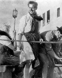 The Duke of Edinburgh, butcher's apron over his whites, holds a huge lather brush in his hand and waits for Father Neptune's next victim in the 'crossing the line' ceremony held aboard the liner 'Gothic', when she sailed across the Equator. Neptune is played by Inspector Frank Kelley, personal police officer to the Duke.